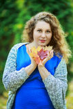 Woman in the park. Young beautiful plussize model in the autumn park Royalty Free Stock Photo