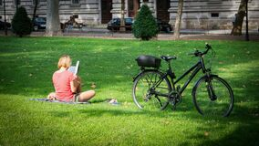 Woman parked a bicycle and reading a book