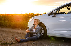 Woman parked at the roadside at sunset Stock Photos