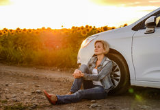 Woman parked at the roadside at sunset Royalty Free Stock Images