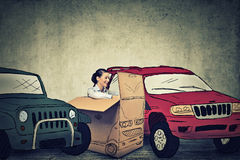 Woman parking her compact car in between large SUV gas guzzlers Royalty Free Stock Photos