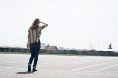 Woman in the parking lot. Woman walking in a windy day on an empty parking lot Stock Image