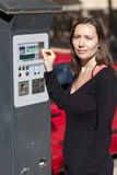 Woman on parking meter Stock Photo