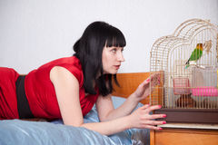 Woman  with  parrot in home Stock Photos
