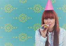 Woman in party hat against yellow sun pattern and blue background Stock Images