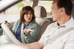 Woman passenger in car with smartphone talking to the driver stock photos
