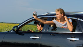 Woman passenger leaning out of car taking photo Stock Photo