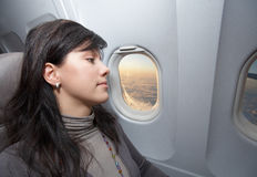 Woman is on passenger seat at airplane Royalty Free Stock Photography