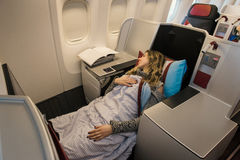 Woman passenger sleeping at the business class of airplane Royalty Free Stock Images