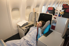 Woman passenger sleeping at the business class of airplane Royalty Free Stock Photo