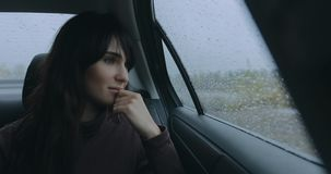 Woman thinking sitting in a car at rainy day looking at window. Woman passenger thinking sitting in a car at rainy day looking at window stock footage
