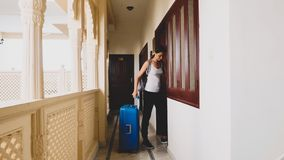 Woman passes into the hotel and rolls the suitcase to her room. stock image
