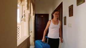 Woman passes into the hotel and rolls the suitcase to her room. Front view. stock video footage