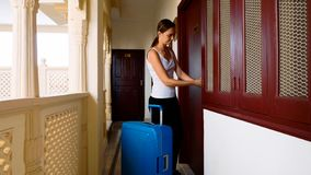Woman passes into the hotel and rolls the suitcase to her room. stock images