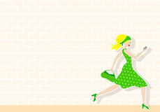 Woman passes by a wall Stock Images