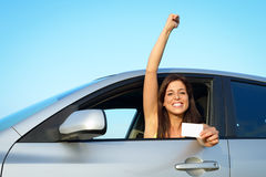 Woman passing car driving license test. Female young driver in her car after passing the driving license test. Successful woman showing blank card in vehicle royalty free stock images