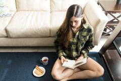 Woman Passing Her Morning By Reading Stories At Home. Young woman with brown hair reading novel while resting on carpet at home royalty free stock photo