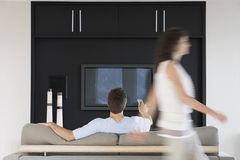 Woman Passing By Man Using Remote Control While Watching TV. Blurred motion of women passing by men using remote control while watching TV at home Stock Photos