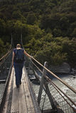 Woman passing a suspension bridge Royalty Free Stock Photos