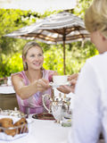 Woman Passing Tea Cup To Friend At Outdoor Cafホ Royalty Free Stock Image