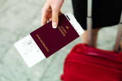 Woman with passport. And airline tickets at an airport waiting for her departure on holiday Stock Photography