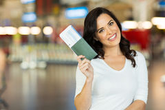Woman passport boarding pass. Portrait of happy young woman holding passport and boarding pass at airport Stock Photo