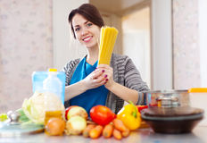 Woman with pasta and vegetables at  kitchen Stock Photography