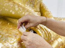 Woman pastes adhesive gold leaf on buddha statue Royalty Free Stock Images