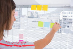 Woman pasting sticky note Stock Image