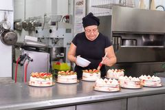 Woman pastry chef smiling and working happy, making cakes at the pastry shop. royalty free stock images