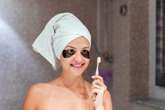 Woman in patches brushing her teeth in the bathroom in the morning. Healty skincare and wellness concept royalty free stock photography