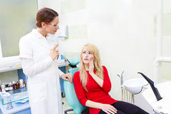 Woman patient in dentist office getting consultation from doctor. Closeup portrait sad girl, patient women with painful tooth, ache siting in chair, medical stock image