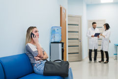 Woman patient in speaking at the mobile phone in hospital waiting room. stock image