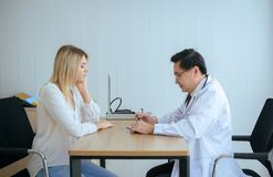 Women patient talking with senior men doctor examining and follow up treatment at hospital ward,Female feeling depressed royalty free stock photo