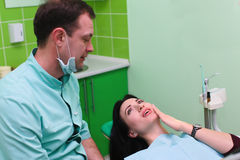 Woman patient talking to male dentist and complain of toothache at dental clinic office Stock Photos
