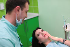 Woman patient talking to male dentist and complain of toothache at dental clinic office Royalty Free Stock Photography