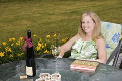 Woman on Patio with Wine and Book stock images