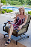 Woman on patio with wine glass. Attractive blond woman sitting on a patio holding a wine glass Stock Photo