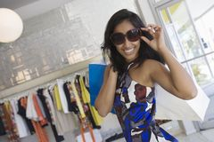 Woman In Patterned Dress Smiles In Sunglasses Royalty Free Stock Photography