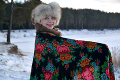 The woman in a pavlovo-posadsky scarf costs on the bank of the lake Royalty Free Stock Image