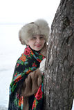 The woman in a pavlovo-posadsky scarf and a fur cap hides behind a tree Royalty Free Stock Photo