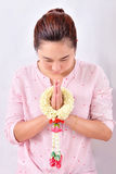 A woman pay homage with Thai traditional jasmine garland on her hands. Symbol of Mother`s day in thailand Royalty Free Stock Image