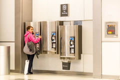 Woman on a pay phone in airport Royalty Free Stock Photo