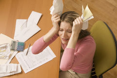Woman Paying Bills. A young woman is paying bills at her desk and has her eyes closed from stress.  Horizontal shot Stock Image