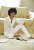 Woman Paying Bills. Young adult African American sitting in living room paying bills Stock Photo