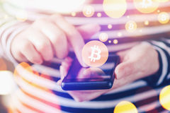 Woman paying with Bitcoins over mobile smartphone. Woman paying with Bitcoins over smartphone, close up of female hands using mobile phone device to complete Stock Photo