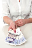 Woman is paying in british currency Royalty Free Stock Photography