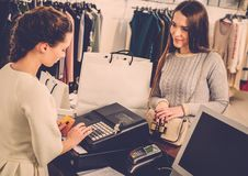 Woman paying card in a showroom. Happy women customer paying with credit card in fashion showroom Royalty Free Stock Photo
