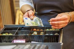 Woman is paying In cash with euro banknotes. Close up on woman is paying in a  bakery  with cash euro banknotes Royalty Free Stock Photos