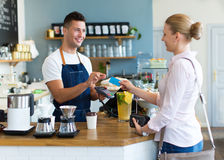 Woman paying for coffee. At the coffee shop Stock Images